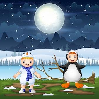 Glückliche kinder im tierkostüm auf verschneite nachtlandschaft