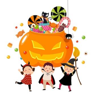 Glückliche kinder in halloween-kostümen, die einen kürbis voller süßigkeiten halten.