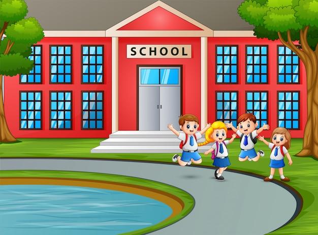 Glückliche kinder in uniform mit rucksack zur schule gehen