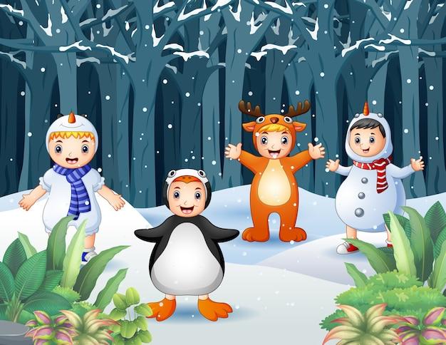 Glückliche kinder in verschiedenen tierkostümen auf schneebedecktem wald