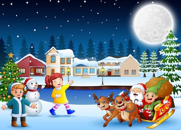 Glückliche kinder mit weihnachtsmann und elf, die seinen pferdeschlitten in der winternacht reiten