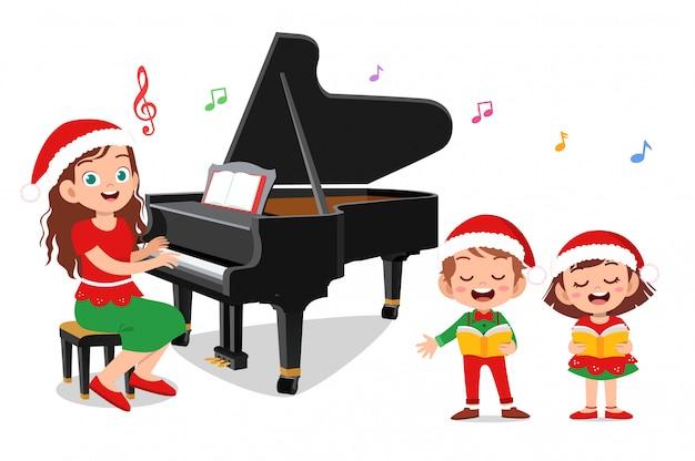 Glückliche kinder singen mit klavier weihnachten