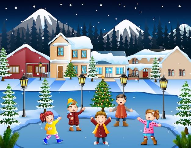 Glückliche kindergruppe, die im schneebedeckten dorf singt