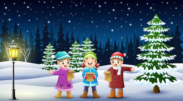 Glückliche kindergruppe, die im schneebedeckten garten singt