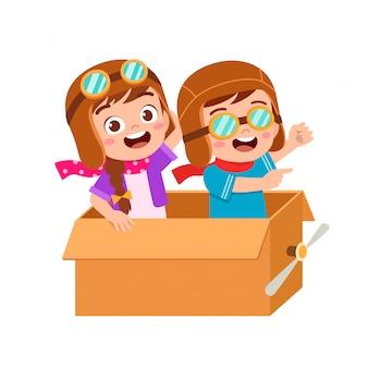 Glückliche kinderjungenspielspielzeug-flugzeugpappe