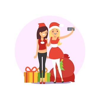 Glückliche lächelnde junge freundinnen, die selfie foto auf weihnachtsfest machen