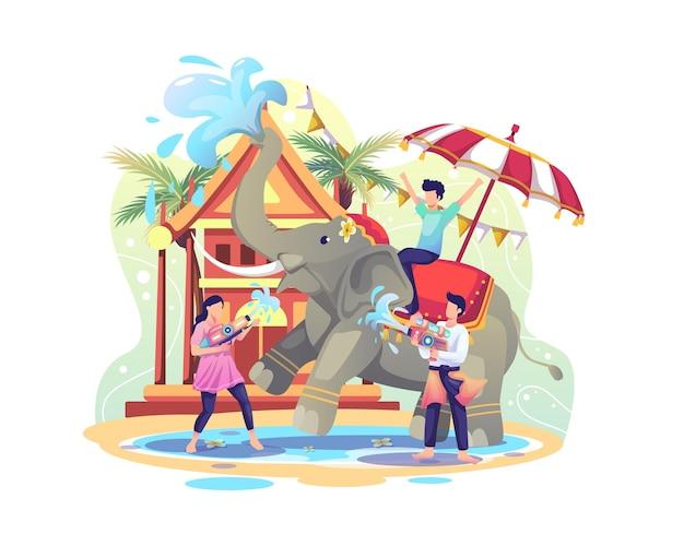 Glückliche leute, die songkran festival feiern, indem sie wasser mit elefanten spielen illustration Premium Vektoren