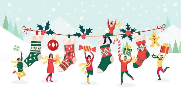 Glückliche leute, die weihnachtsfeier feiern. charaktere steckt geschenke, süßigkeiten in große festliche socken. vorbereitung auf die winterferien. heiligabend. frohe weihnachten und neujahr