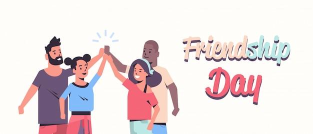 Glückliche leute gruppieren mit ihren händen, die auf einander gestapelt werden junge freunde, die spaß zusammen freundschaftstag-feier-grußkarte haben