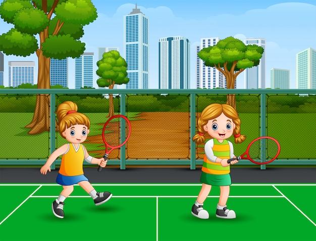 Glückliche mädchen, die tennis am gericht spielen