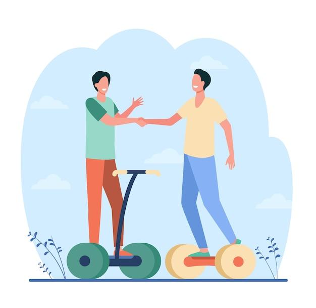 Glückliche männliche freunde, die hände schütteln. jungs reiten auf hoverboards und treffen sich draußen