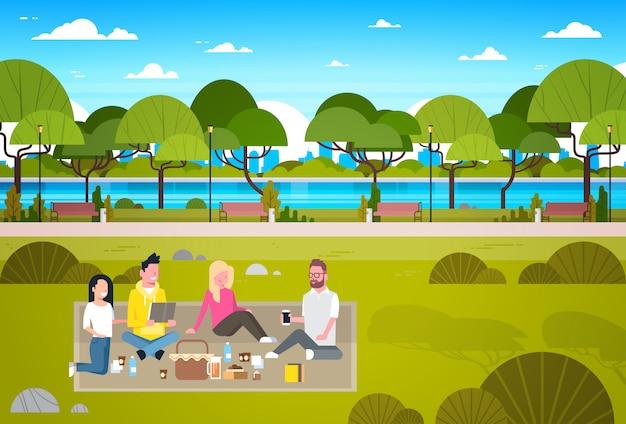 Glückliche menschen, die picknick in der park-gruppe jungen männern und frauen sitzen auf dem entspannenden gras haben