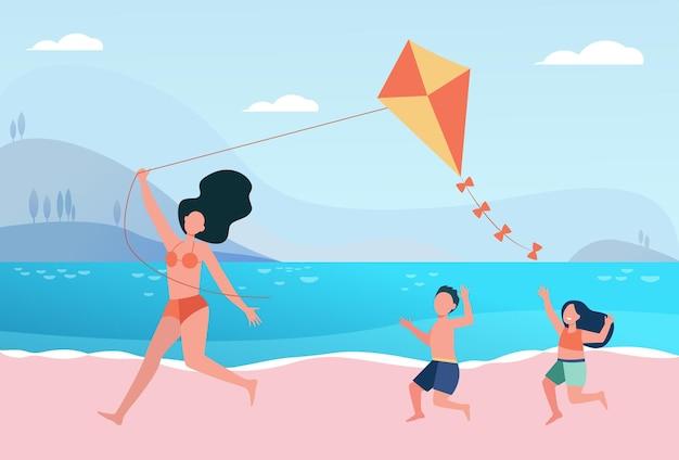 Glückliche mutter mit kindern, die drachen am strand fliegen. familie, die spaß am meer hat