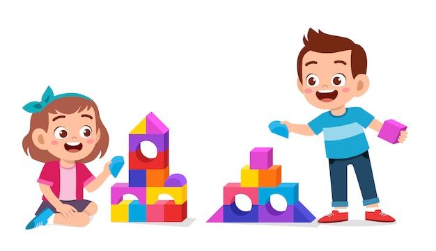 Glückliche nette kinder spielen ziegelsteinblock zusammen