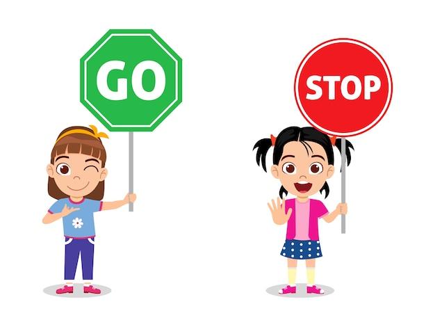 Glückliche niedliche kindermädchen, die verkehrszeichen halten halten und lokalisiert auf weißem hintergrund gehen
