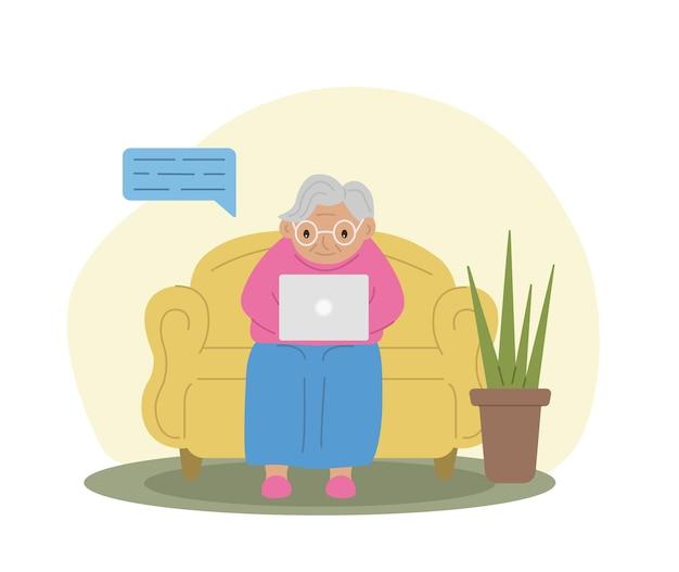 Glückliche oma mit laptop-technik und die ältere oma sitzt auf der couch