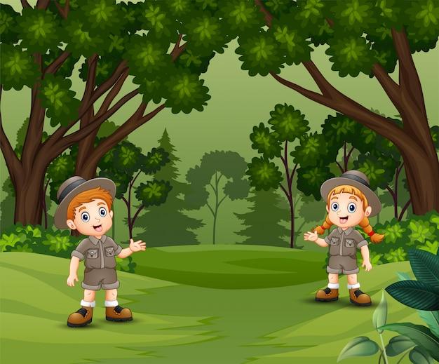Glückliche pfadfinderkinder, die den wald sprechen und erforschen