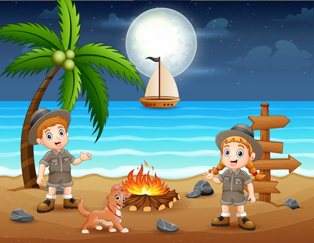 Glückliche pfadfinderkinder, die lagerfeuer am strand genießen