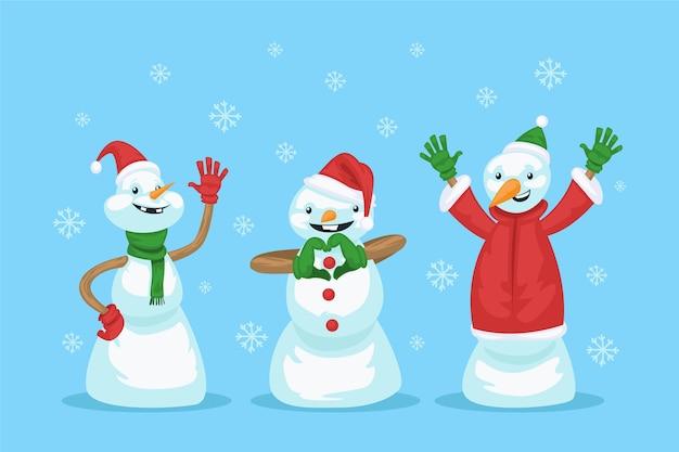 Glückliche schneemänner, die rote und grüne kleidung tragen