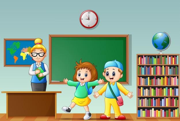 Glückliche schule scherzt mit weiblichem lehrer in einem klassenzimmer