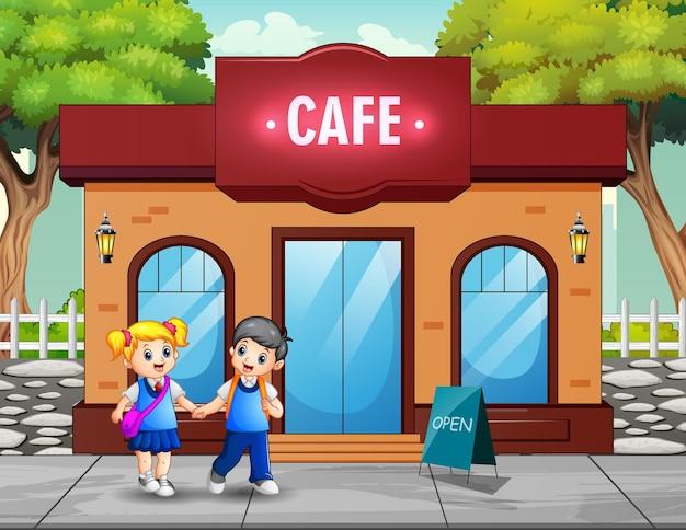 Glückliche schulkinder, die an einem café vorbeigehen