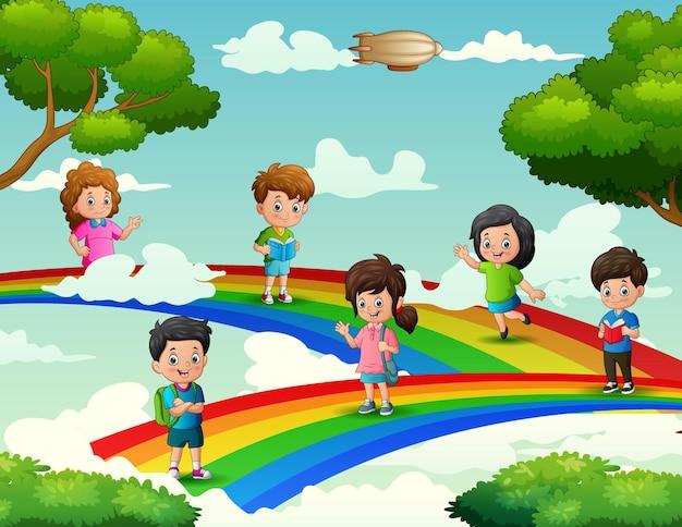 Glückliche schulkinder, die auf dem regenbogen stehen Premium Vektoren