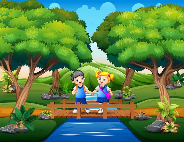 Glückliche schulkinder, die holzbrücke kreuzen