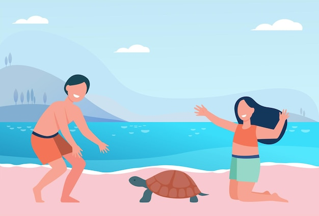Glückliche süße kinder, die mit schildkröte am strand spielen