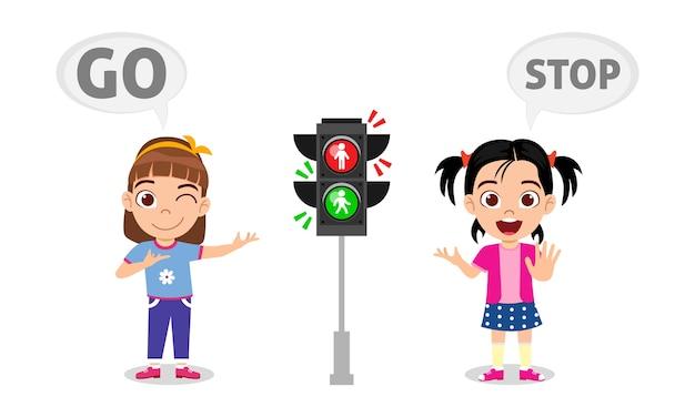 Glückliche süße kindermädchen mit verkehrszeichen halten an und gehen