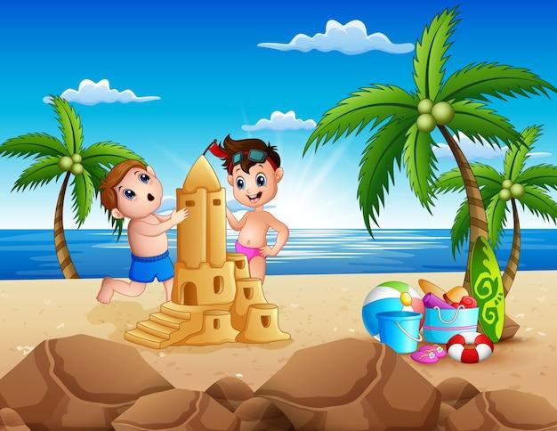Glückliche zwei jungen, die sandburg am strand machen