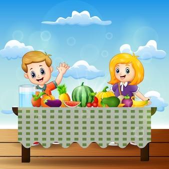 Glückliche zwei kinder mit gerichten vieler arten von früchten