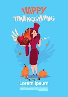 Glücklicher erntedankfest-weiblicher chefkoch holding turkey restaurant autumn traditional-menü-konzept-gruß-karte