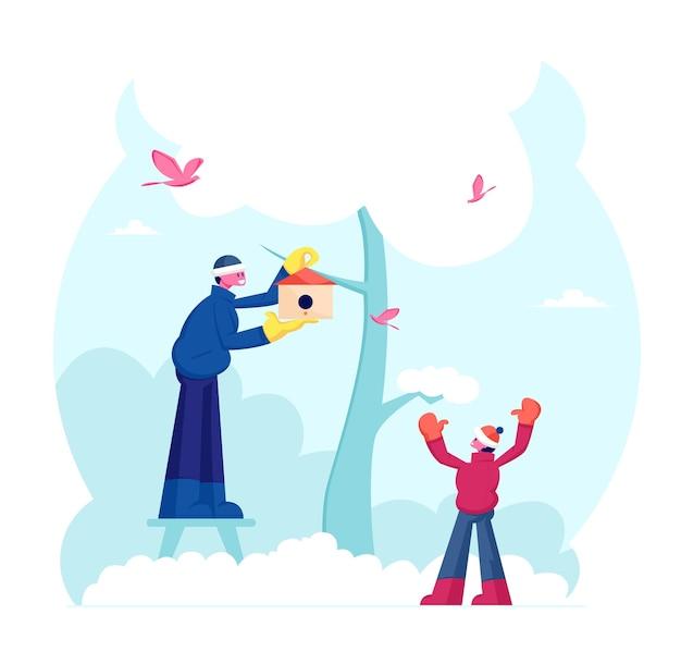 Glücklicher familienvater und kleiner sohn, die vogelhaus auf baum im winter hängen. karikatur flache illustration
