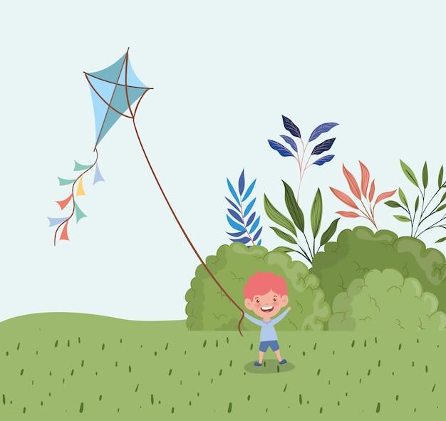 Glücklicher fliegendrachen des kleinen jungen in der landschaft