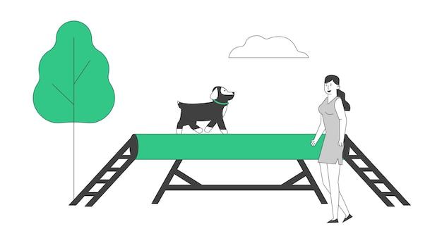 Glücklicher frauentrainingshund im park oder im speziellen bereich, mädchen, das mit welpen spielt.