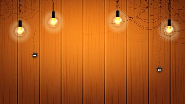 Glücklicher halloween-hintergrund mit glühlampe und spinnennetz auf hölzerner wand mit hängenden spinnen.