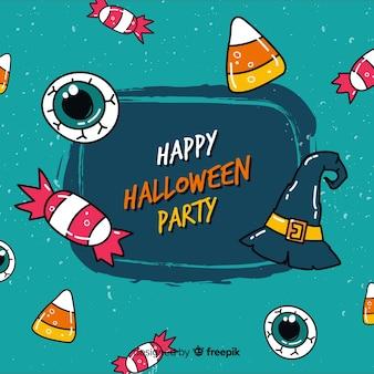 Glücklicher halloween-hintergrund mit hexenhut und -süßigkeiten