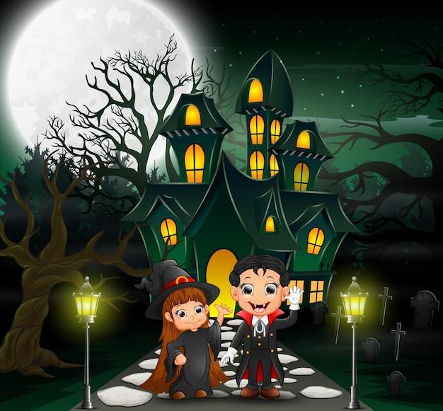 Glücklicher halloween-vampir und -hexe vor dem geisterhaus