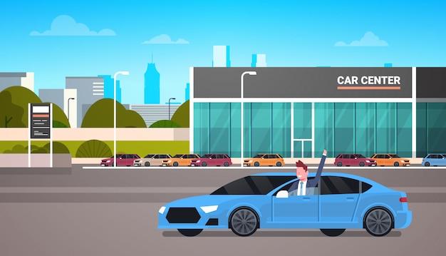 Glücklicher inhaber driving new car über verkaufsstelle-mitte-ausstellungsraum-gebäude