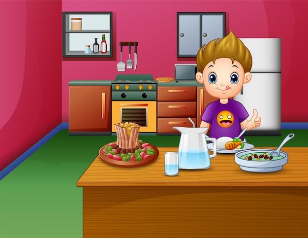 Glücklicher junge, der am speisetische isst