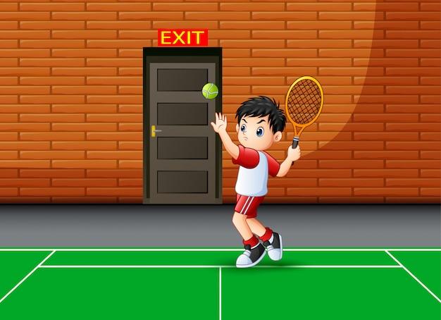 Glücklicher junge, der das tennis innen spielt