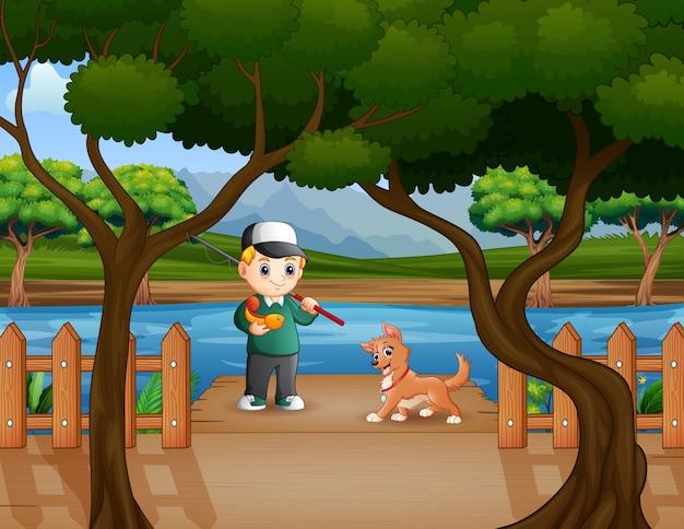 Glücklicher junge, der mit einem hund am pier fischt