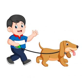 Glücklicher junge, der mit seinem hund geht