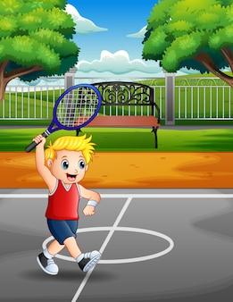 Glücklicher junge, der tennis an den gerichten spielt
