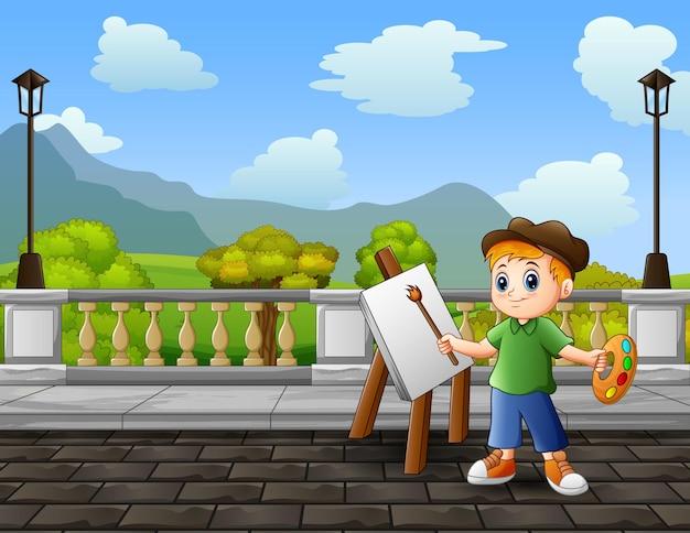 Glücklicher junge malt landschaften auf einer leinwand