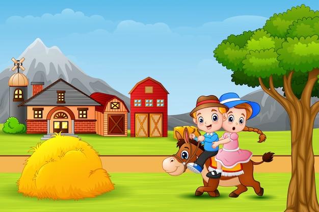 Glücklicher junge und mädchen, die ein pferd in der faram landschaft reitet