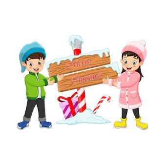 Glücklicher junge und mädchen in der winterkleidung mit holzschild