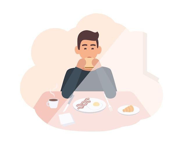 Glücklicher junger mann, der am tisch sitzt und köstliche morgenmahlzeit isst. männlicher charakter, der zu hause frühstückt