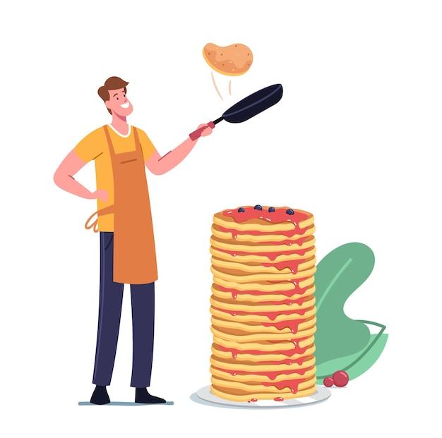 Glücklicher junger mann in schürze, der pfannkuchen auf pfanne mit stapel von gebackenen zum frühstück braten