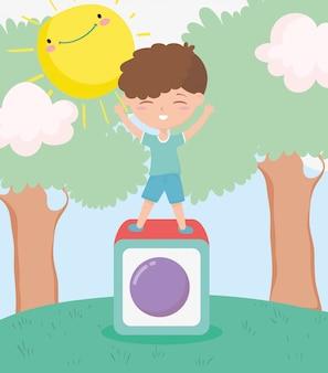 Glücklicher kindertag, kleiner junge, der im blockspielzeugkarikatur spielt